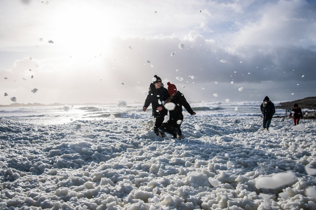 People walk in the foam in the La Torche beach in Plomeur, western France, on December 28, 2020, as storm Bella caused torrential rain and heavy winds in much of France. (Photo by Loic Venance/AFP Photo)