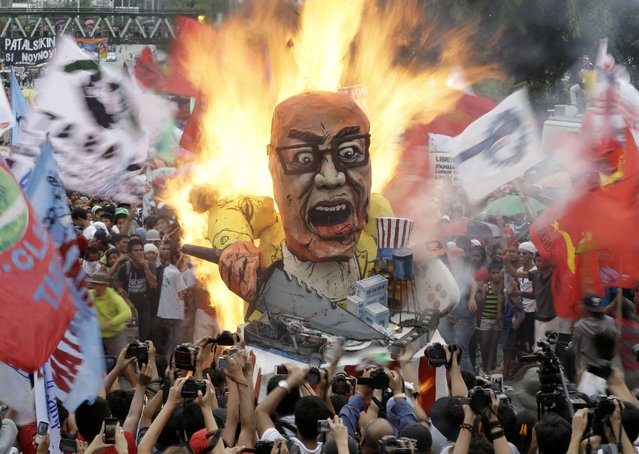 Protesters burn an effigy of Philippine President Benigno Aquino III during a rally to coincide with his fourth State-of-the-Nation Address (SONA) before the country's congressmen and senators Monday July 22, 2013 at the House of Representatives at suburban Quezon city, northeast of Manila, Philippines. President Aquino III is expected to dwell on the gains of his administration particularly on the robust economy but the protesters see otherwise especially on the increasing prices of oil and basic services as water and electricity. (Photo by Bullit Marquez/AP Photo)