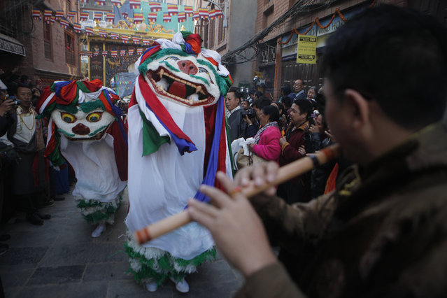 Tibetan Buddhists in traditional attire dance during the last day of the purification ceremony of Boudhanath Stupa in Kathmandu, Nepal, Sunday, November 20, 2016. A three-day purification ceremony was organized to purify the Boudhanath Stupa, which was damaged in the 2015 earthquake, after the completion of its reconstruction. The Stupa will officially open to the public on Nov 22. (Photo by Niranjan Shrestha/AP Photo)