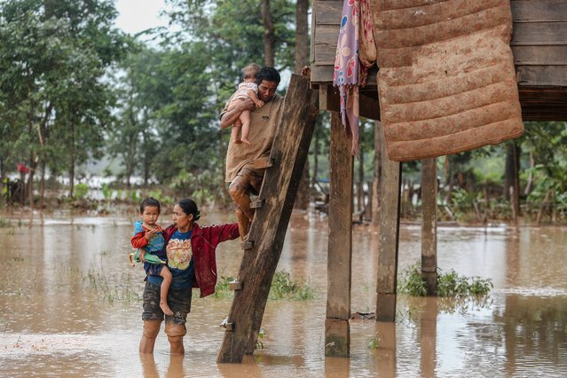 A couple carry their children from their home in the flooded area in Sanamxai, Attapeu province, on July 26, 2018. (Photo by Kao Nguyen/AFP Photo)