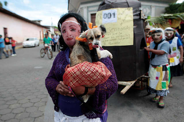 A masked man holds his dog, as he  takes part in festivities in honour of patron saint San Jeronimo in Masaya city, Nicaragua November 20, 2016. (Photo by Oswaldo Rivas/Reuters)