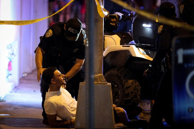 Police officers detain a man as they enforce an 8pm curfew imposed by local authorities on spring break festivities, amid the coronavirus disease (COVID-19) pandemic, in Miami Beach, Florida, U.S., March 20, 2021. (Photo by Marco Bello/Reuters)