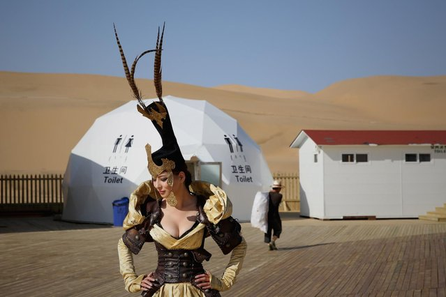 A model in Mongolia costumes prepares backstage in Xiangshawan Desert, also called Sounding Sand Desert on July 18, 2013 in Ordos of Inner Mongolia Autonomous Region, China. Xiangshawan is China's famous tourist resort in the desert. It is located along the middle section of Kubuqi Desert on the south tip of Dalate League under Ordos City. Sliding down from the 110-metre-high, 45-degree sand hill, running a course of 200 metres, the sands produce the sound of automobile engines, a natural phenomenon that nobody can explain. (Photo by Feng Li/Getty Images)