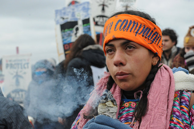 A protester cries while watching a demonstration on Turtle Island on Thanksgiving day during a protest against plans to pass the Dakota Access pipeline near the Standing Rock Indian Reservation, near Cannon Ball, North Dakota, U.S. November 24, 2016. (Photo by Stephanie Keith/Reuters)