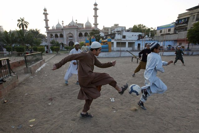 A madrasa (religious school) student kicks a ball while playing in a soccer match with others on the grounds outside a mosque in Karachi's slum January 28, 2015. (Photo by Akhtar Soomro/Reuters)