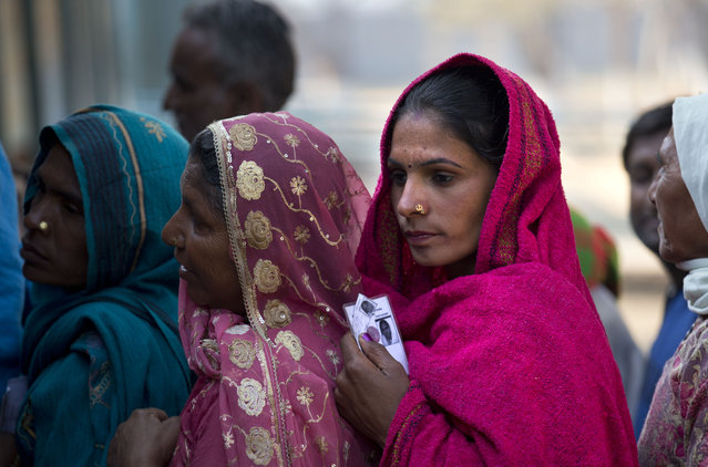 Indian women wait in a queue to cast their votes at a polling booth in New Delhi, India, Saturday, February 7, 2015. Voters cast ballots in the Indian capital on Saturday in an election that is seen as a litmus test for the popularity of Prime Minister Narendra Modi and his Hindu nationalist party. (Photo by Manish Swarup/AP Photo)