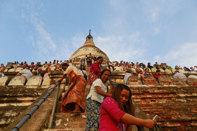 People stand on the Shwesandaw Pagoda as they wait to see the sunset in the ancient city of Bagan February 13, 2015. (Photo by Soe Zeya Tun/Reuters)