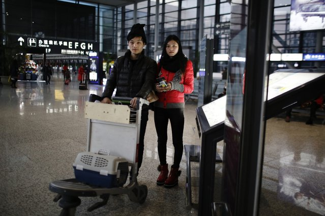 Ma and his girlfriend Wei pose for a portrait at Hongqiao airport in Shanghai, February 12, 2015. The couple travelled to Henan province by plane to spend Chinese New Year with his family. (Photo by Carlos Barria/Reuters)