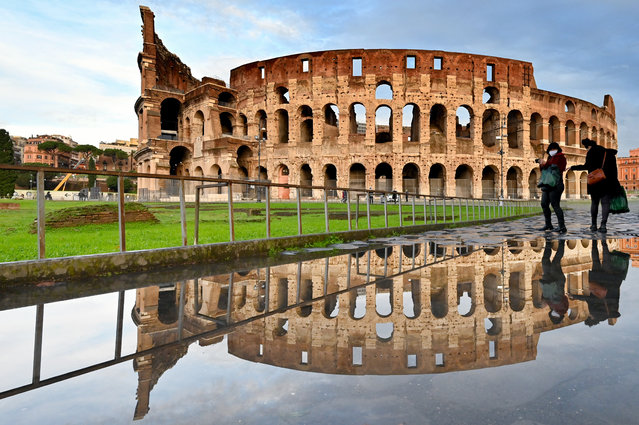 People walk past the Colosseum monument in Rome reflected in a pool of water on December 8, 2020 following heavy rains. (Photo by Alberto Pizzoli/AFP Photo)
