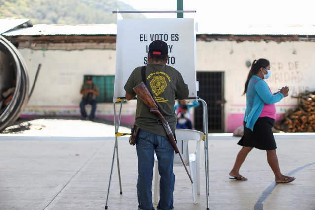 A community police officer fills out his ballot at a polling station during mid-term election in Alyahualtempa, Guerrero state, Mexico, June 6, 2021. (Photo by Edgard Garrido/Reuters)
