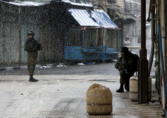Israeli soldiers stand guard during a snow storm in West Bank old city of Hebron, January 26, 2016. (Photo by Mussa Qawasma/Reuters)