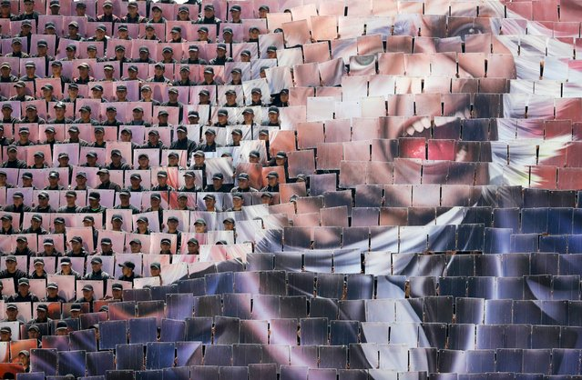 The image of a face appears as hundreds of military troops holding mosaic cards raise them in a wave, during a review of the troops that will march in the Independence Day parade, in Mexico City, September 14, 2016. (Photo by Rebecca Blackwell/AP Photo)