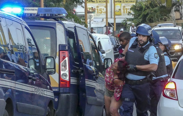 A protester is dragged away and arrested by a police officer after she was seen with others blocking the traffic in Sainte Marie, while protesting against the rising of the fuel and oil prices, in the Indian Ocean island of Reunion, Thursday, November 22, 2018. France is deploying soldiers to stem violence in the Indian Ocean island of Reunion after protests over fuel tax hikes degenerated into looting and rioting. (Photo by Fabrice Wislez/AP Photo)