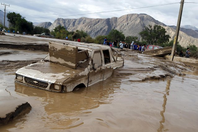 A damaged car covered in mud lies on a street at Copiapo city, March 26, 2015. (Photo by Ivan Alvarado/Reuters)
