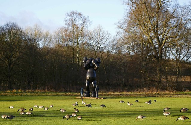 """Visitors look at a sculpture entitled """"At This Time"""" by American artist Kaws at the Yorkshire Sculpture Park in Wakefield, Britain February 3, 2016. (Photo by Darren Staples/Reuters)"""