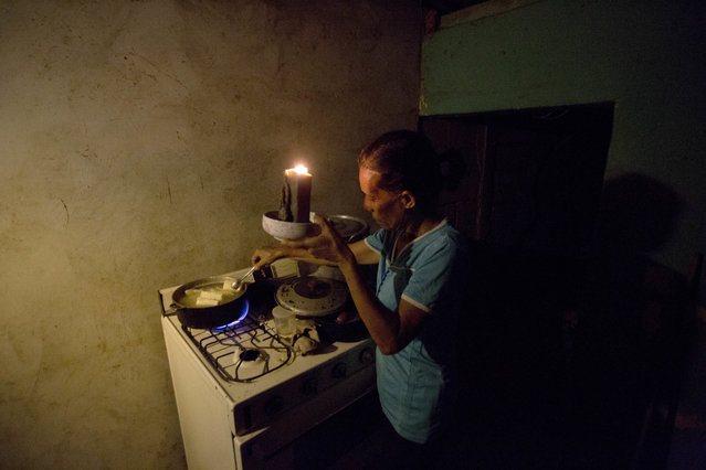 """In this August 19, 2018 photo, Mireya Marquez uses candlelight to cook her dinner of boiled """"cassava"""", also known as yuca and manioc, during a blackout in Maracaibo, Venezuela. For months Maracaibo's residents have endured rolling blackouts, but things turned dire on August 10 when a fire destroyed a main power line supplying the city of 1.5 million people. (Photo by Fernando Llano/AP Photo)"""