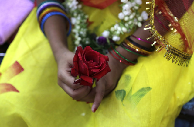 """A young Hindu girl holds a rose in her hand during a ceremony where she and other girls are worshipped as """"Kumari"""", or living goddess, during Ram Navami festival, at a temple in Kolkata, India, Saturday, March 28, 2015. (Photo by Bikas Das/AP Photo)"""