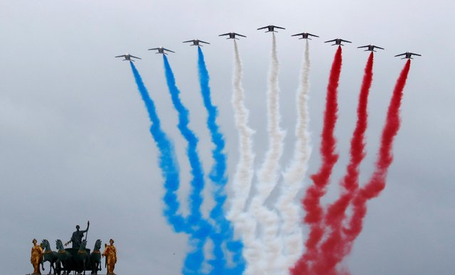 Alpha jets from the French Air Force Patrouille de France fly past Carrousel du Louvre during the Bastille Day celebrations in Paris, France, July 14, 2021. France is celebrating its national holiday with thousands of troops marching in a Paris parade and traditional parties around the country, after last year's events were scaled back because of virus fears. (Photo by Gonzalo Fuentes/Reuters)