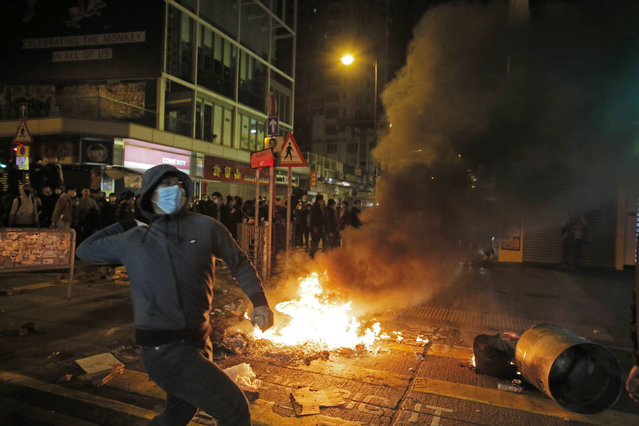 A rioter tries to throw bricks at police in Mong Kok district of Hong Kong, Tuesday, February 9, 2016. (Photo by Vincent Yu/AP Photo)