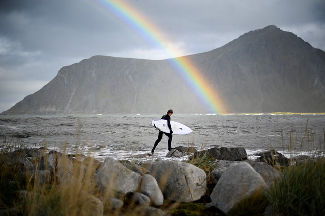 Surfer Anker Olsen Frantzen, 17, of Norway, walks to the water for a free surf session on September 26, 2018, in Flackstad, Northern Norway, the eve of the Lofoten Masters 2018. Lofoten Masters 2018, the most northern Surf contest, will be held from September 27 to 30, in Unstad, within Arctic circle. (Photo by Olivier Morin/AFP Photo)