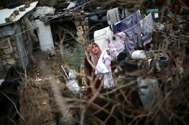 A Palestinian woman hangs laundry on a rope to dry outside her dwelling in Khan Younis in the southern Gaza Strip December 19, 2016. (Photo by Ibraheem Abu Mustafa/Reuters)
