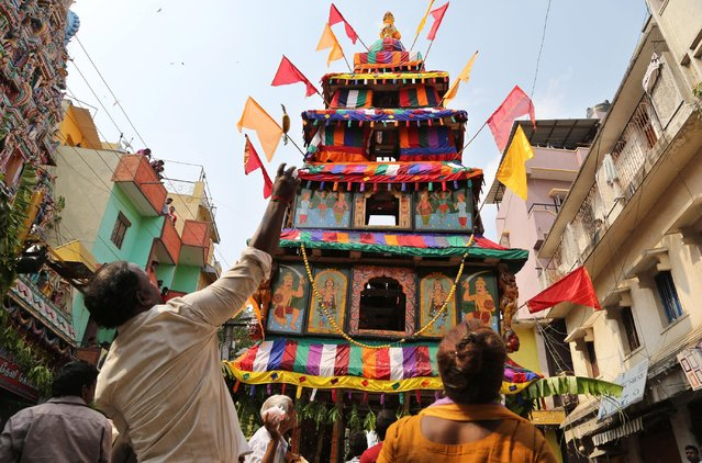 Indian devotees throw bananas and rock salt as offerings to a chariot carrying the effigy of Hindu goddess Muthyalamma during the annual festival in her honor in Bangalore, India, Wednesday, April 1, 2015. The 16-day festival is one of the oldest continuously celebrated festivals of Bangalore. (Photo by Aijaz Rahi/AP Photo)