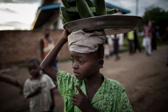 A young vendor carries her wares on her head as she walks along a street in the village of Baraka, South Kivu on March 23, 2015. (Photo by Federico Scoppa/AFP Photo)