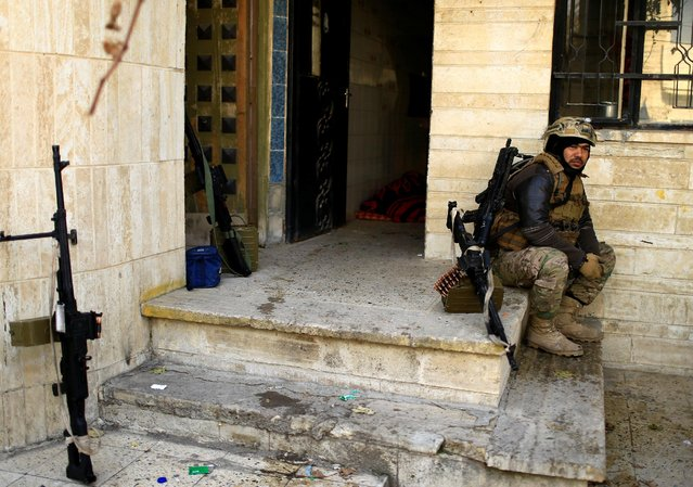 A member of Iraqi rapid response forces sits during a battle with Islamic State militants in the Mithaq district of eastern Mosul, Iraq, January 3, 2017. (Photo by Thaier Al-Sudani/Reuters)