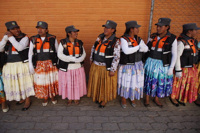 In this November 28, 2013 photo, Aymara women traffic cops speak during a training session before heading out to control the vehicular traffic on the streets of El Alto, Bolivia. (Photo by Juan Karita/AP Photo)