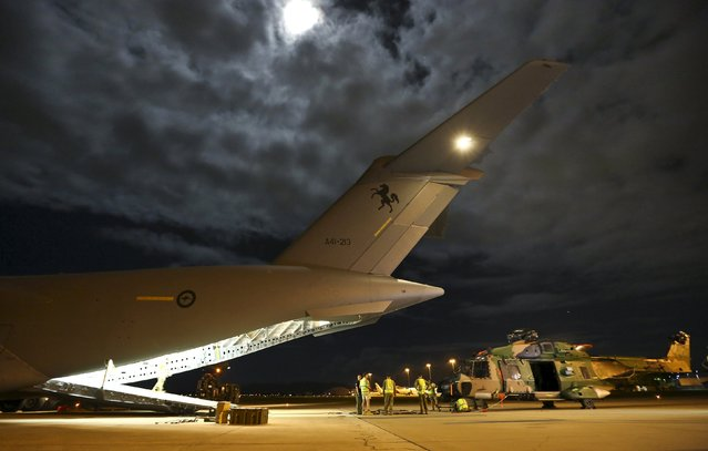 Australian Air Force and Army personnel load a Multi Role Helicopter (MRH 90) onto an Australian Air Force C-17 aircraft before departing from RAAF Base Townsville en route to assist in Cyclone Winston-ravaged Fiji, in Australia, this handout image supplied by the Australian Defence Force February 23, 2016. (Photo by Reuters/Australian Defence Force)