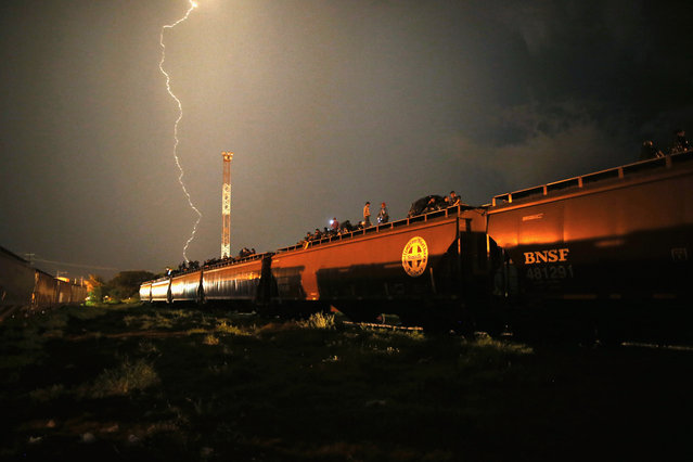 """Central American migrants stand atop a freight train  headed north early on August 4, 2013 in Arriaga, Mexico. Thousands of immigrants ride atop the trains, known as """"la bestia"""", or the beast, during their long and perilous journey through Mexico to the U.S. border. (Photo by John Moore/Getty Images)"""