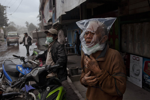 A man wears a plastic bag to cover his face from ash after their village hit by ash from eruption of Mount Sinabung in Payung village on January 8, 2014 in Karo District, North Sumatra, Indonesia. (Photo by Ulet Ifansasti/Getty Images)