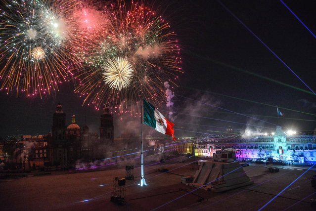 """Fireworks lit the sky over the Zocalo Square during the ceremony for the 211th anniversary of the """"Cry of Independence"""" (El Grito) in Mexico City, Mexico, 15 September 2021, marking the start of Independence Day celebrations. Mexican President Andres Manuel Lopez Obrador re-enacted the """"Cry of Independence"""" (El Grito) for the second consecutive year without the presence of citizens in the Zocalo in central Mexico City due to the COVID-19 pandemic. (Photo by Mario Guzman/EPA/EFE)"""