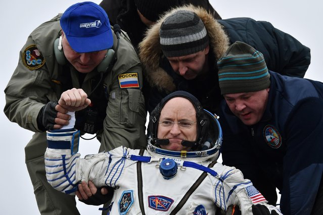 Ground personnel help International Space Station (ISS) crew member Scott Kelly of the U.S. to get off the Soyuz TMA-18M space capsule after landing near the town of Dzhezkazgan, Kazakhstan, Wednesday, March 2, 2016. (Photo by Krill Kudryavtsev/Pool Photo via AP Photo)