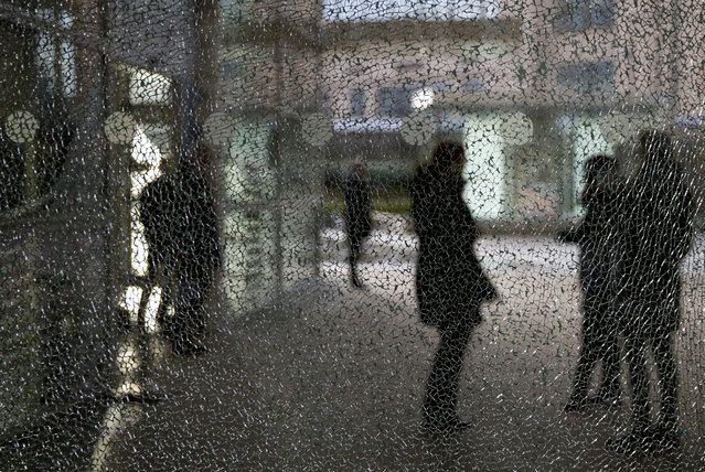 People stand behind a shattered glass outside the EU headquarters in Brussels, Wednesday, January 9, 2019. The window was shattered during a recent demonstration. (Photo by Virginia Mayo/AP Photo)
