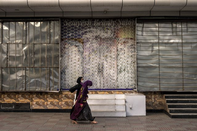 Afghan women walk past a closed beauty salon in Kabul, Afghanistan, Saturday, September 11, 2021. Since the Taliban gained control of Kabul, several images depicting women outside beauty salons have been removed or covered up. (Photo by Bernat Armangue/AP Photo)