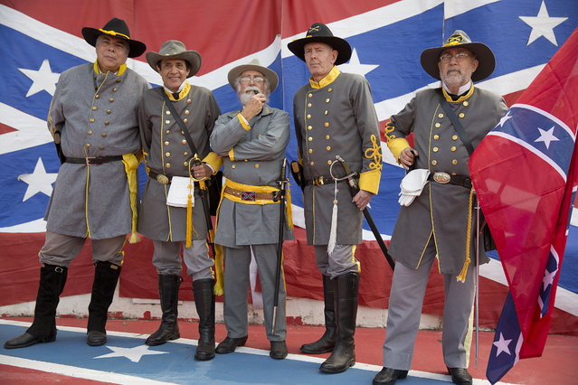 Descendants of American Southerners wearing Confederate-era uniforms pose for pictures as they attend a party to celebrate the 150th anniversary of the end of the American Civil War in Santa Barbara d'Oeste, Brazil, Sunday, April 26, 2015. (Photo by Andre Penner/AP Photo)