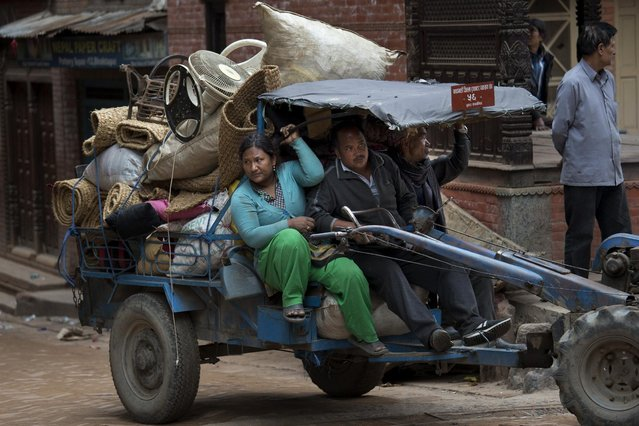Residents carry their belongings that were retrieved from ruins of their homes after Saturday's earthquake in Bhaktapur, Nepal, Tuesday, April 28, 2015. (Photo by Bernat Armangue/AP Photo)