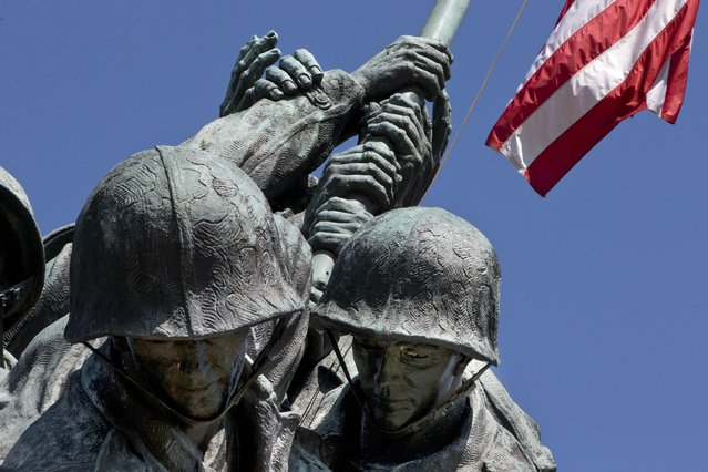 An American flag flies over the U.S. Marine Corps Memorial in Arlington, Va., Wednesday, April 29, 2015. The famous bronze U.S. Marine Corps War Memorial overlooking Washington that depicts Marines raising the American flag at Iwo Jima during World War II has begun turning green with age but now will be restored with a $5.37 million gift. (Photo by Jacquelyn Martin/AP Photo)