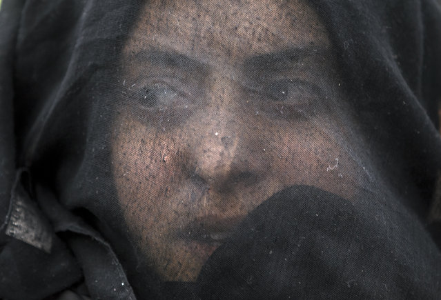 A woman shouts slogans during a protest by migrants demanding the opening of the border between Greece and Macedonia at the northern Greek border station of Idomeni, Sunday, March 12, 2016. Up to 14,000 people are stranded on the outskirts of the village of Idomeni in a makeshift camp. (Photo by Vadim Ghirda/AP Photo)
