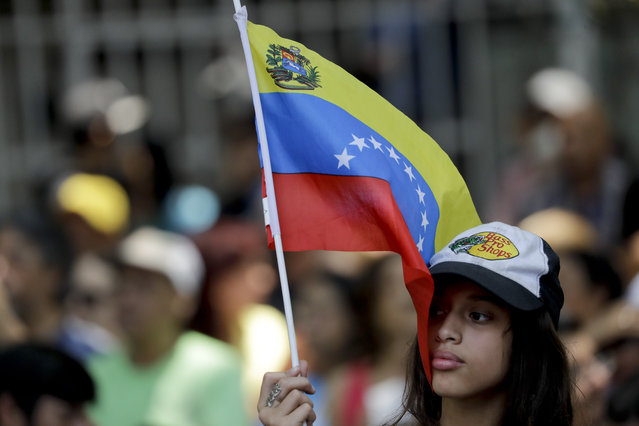 """A supporter of opposition leader Juan Guaido, self-proclaimed interim president of Venezuela, listens to him as he talks about """"Operation Liberty"""", in Caracas, Venezuela, Wednesday, March 27, 2019. (Photo by Natacha Pisarenko/AP Photo)"""
