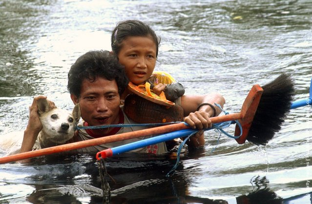 A man, girl and dog cross deep water at Sirombu village December 29, 2004 in Nias, North Sumatra, Indonesia