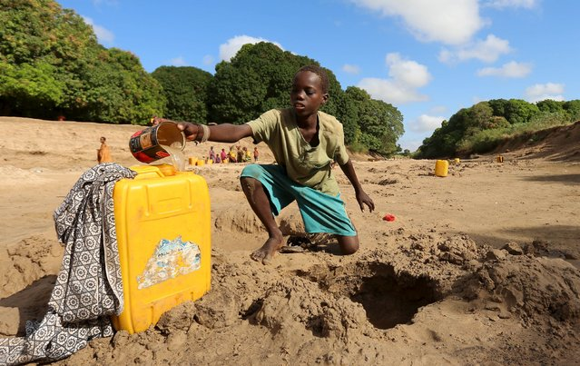 A Somali boy collects water from a well dug in the Shabelle River bed, which is dry due to drought in Somalia's Shabelle region, March 19, 2016. (Photo by Feisal Omar/Reuters)