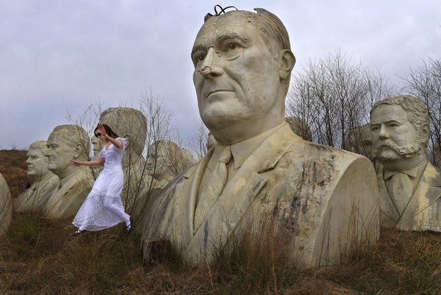 Hannah Rice, 18, jumps from a stump after posing for a photograph next to a large bust of President Franklin D. Roosevelt while touring busts of U.S. presidents in Williamsburg, Va. on March 30, 2019. The statues were once part of an attraction called Presidents Park, which has since closed. (Photo by Matt McClain/The Washington Post)
