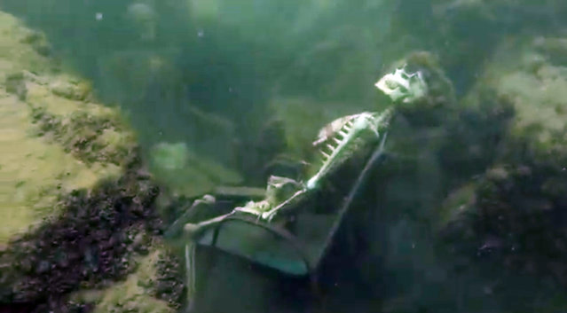 In this frame from video provided by the La Paz Sheriffs' Office, fake skeletons are strategically placed to appear as if they were sitting together with their lawn chairs bound to large rocks in the Colorado River near the Arizona and California border. A man snorkeling came across the two fake skeletons sitting in lawn chairs about 40 feet underwater and reported the skeletons to the La Paz County Sheriff's Office on Monday, May 4, 2015. (Photo by AP Photo/La Paz Sheriff's Office)