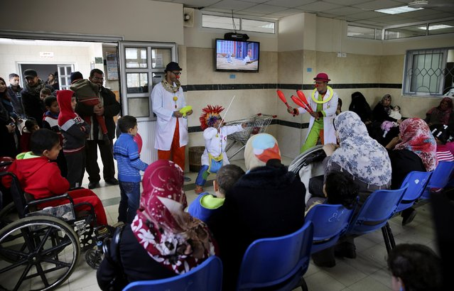 In this Thursday, March 17, 2016 photo, Palestinian clown doctors, 24-year-old Majed Kaloub, top center, and 33-year-old Alaa Miqdad, bottom center, perform for children during their visit at the Al-Rantisi children's hospital in Gaza City. (Photo by Adel Hana/AP Photo)