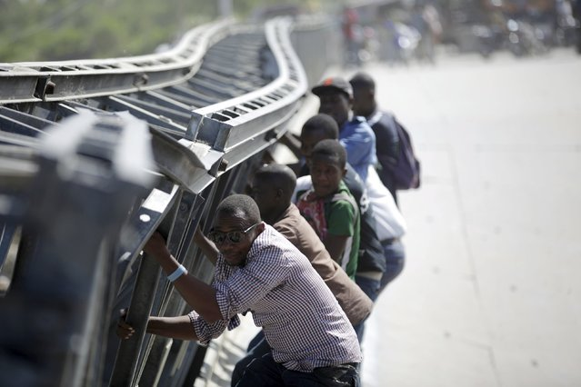 Haitians cross a collapsed bridge on the outskirts of Port-au-Prince, Haiti, March 24, 2016. The bridge collapsed as a truck was crossing it on March 18, according to local media. (Photo by Andres Martinez Casares/Reuters)