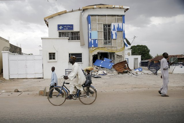 People walk past a bank which locals say was looted by terrorist group Boko Haram, in Mubi, Adamawa state May 10, 2015. (Photo by Akintunde Akinleye/Reuters)