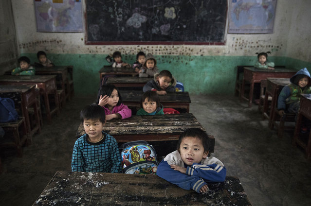"""""""Left behind"""" child Luo Lie, 5, foreground right, listens as he sits in class at a local school on December 16, 2016 in Anshun, China. (Photo by Kevin Frayer/Getty Images)"""