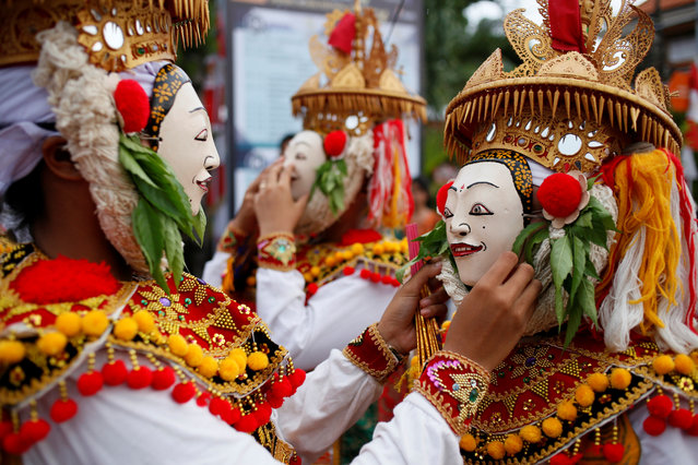 Balinese Hindus wear masks as they prepare before performing sacred Telek dance at a festival in Klungkung, Bali, Indonesia, April 28, 2019. (Photo by Johannes Christo/Reuters)